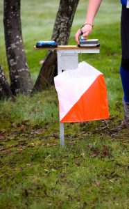 Orienteering runner taking an Control with RF-id based Control system. Focus on the Control